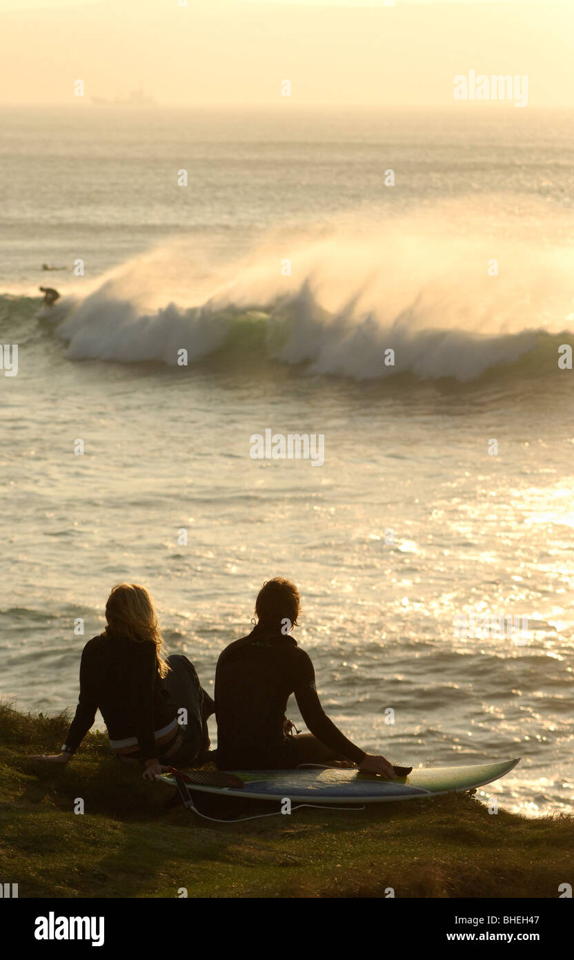 Young surfing couple sitting on surf baord on the edge of the cliff watching the waves breaking - Stock Image