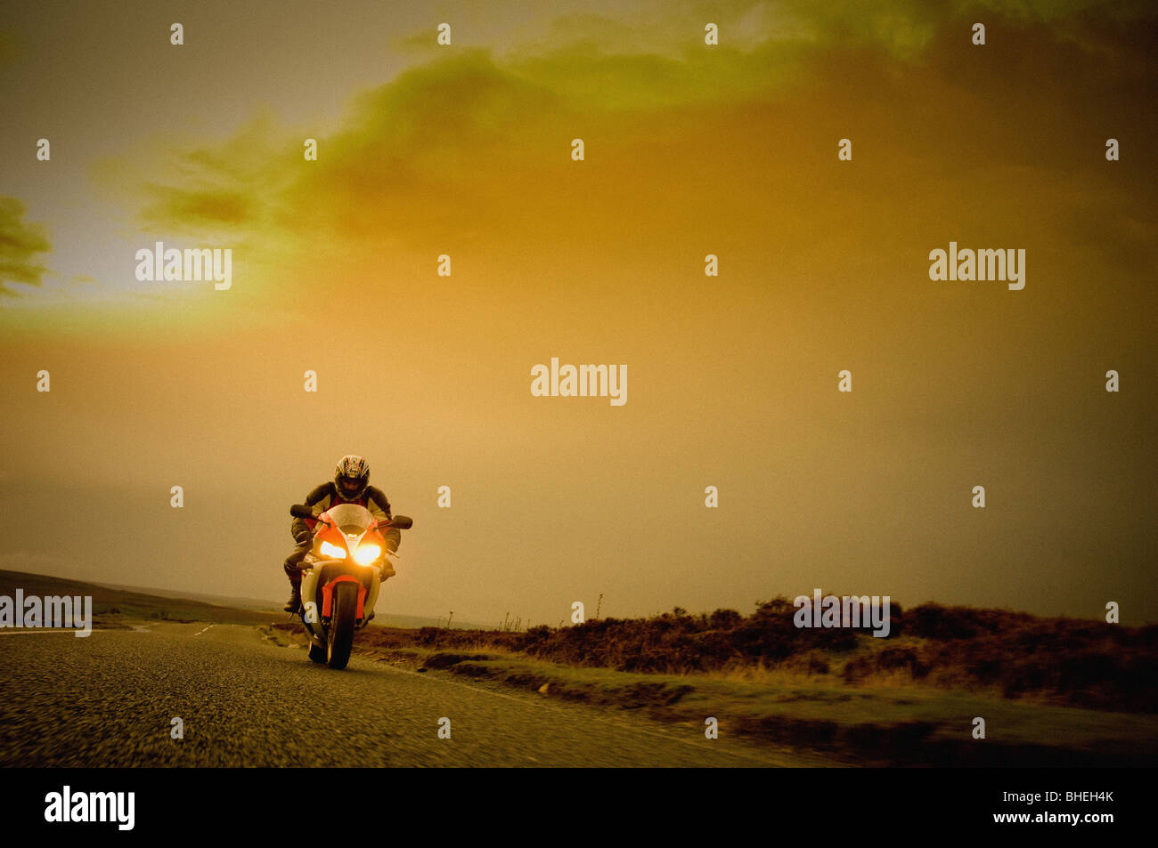 Front view of motorbike and rider on road in the North Yorkshire Moors, UK - Stock Image
