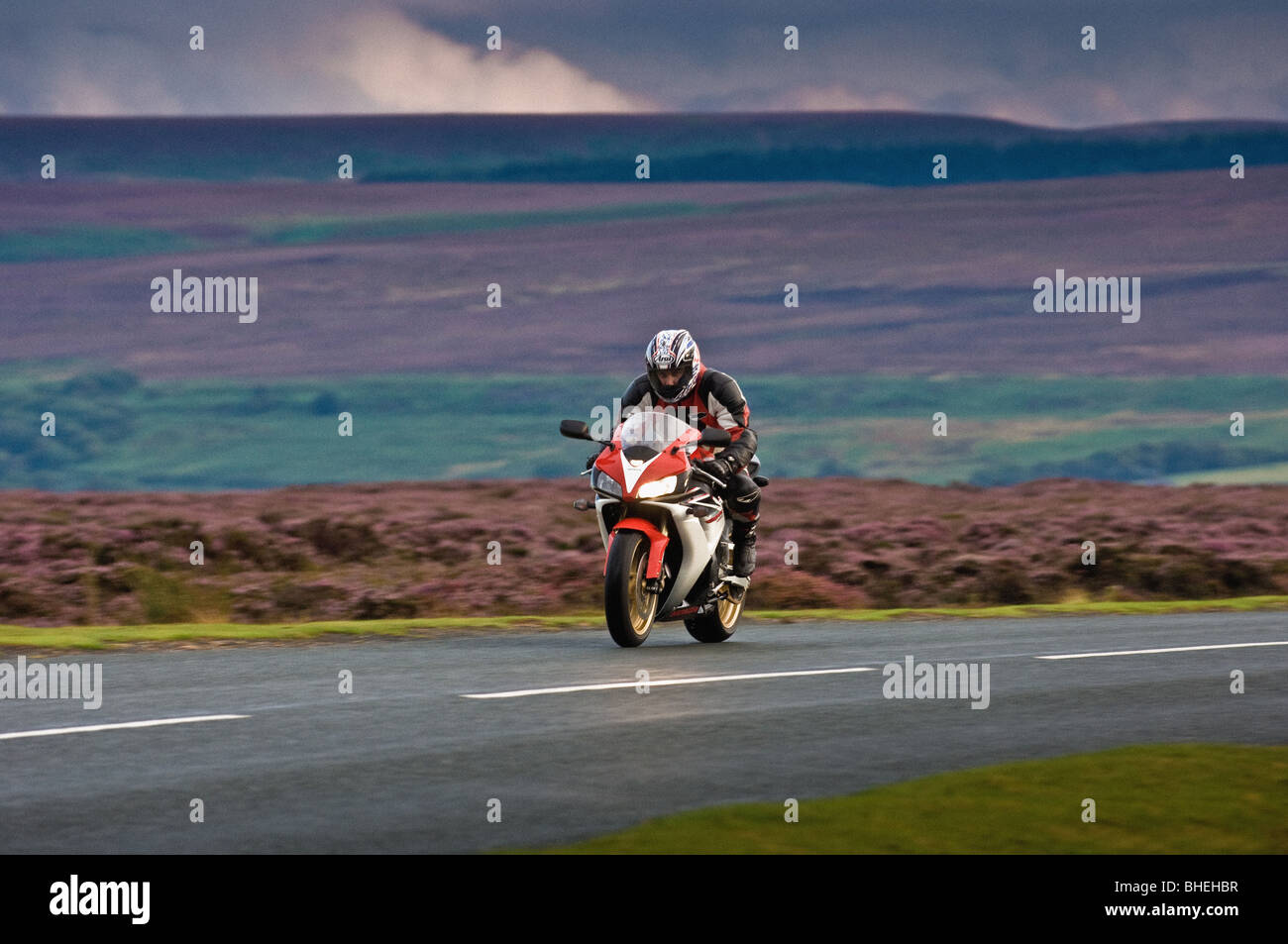 Motorbike and rider on road in the North Yorkshire Moors, UK - Stock Image