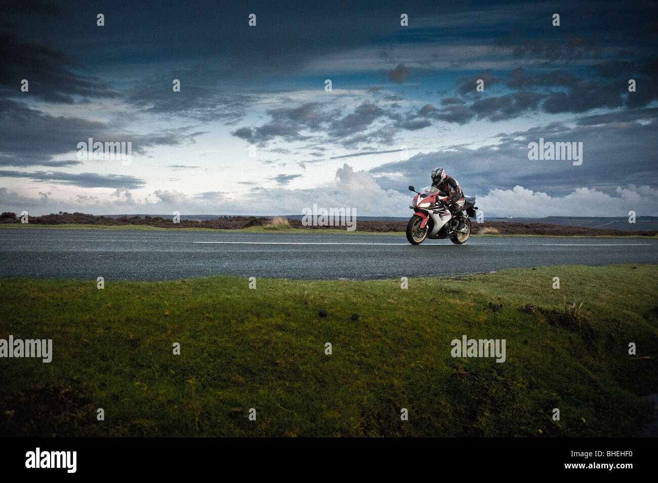 Side view of motorbike and rider on road, North Yorkshire Moors, UK - Stock Image