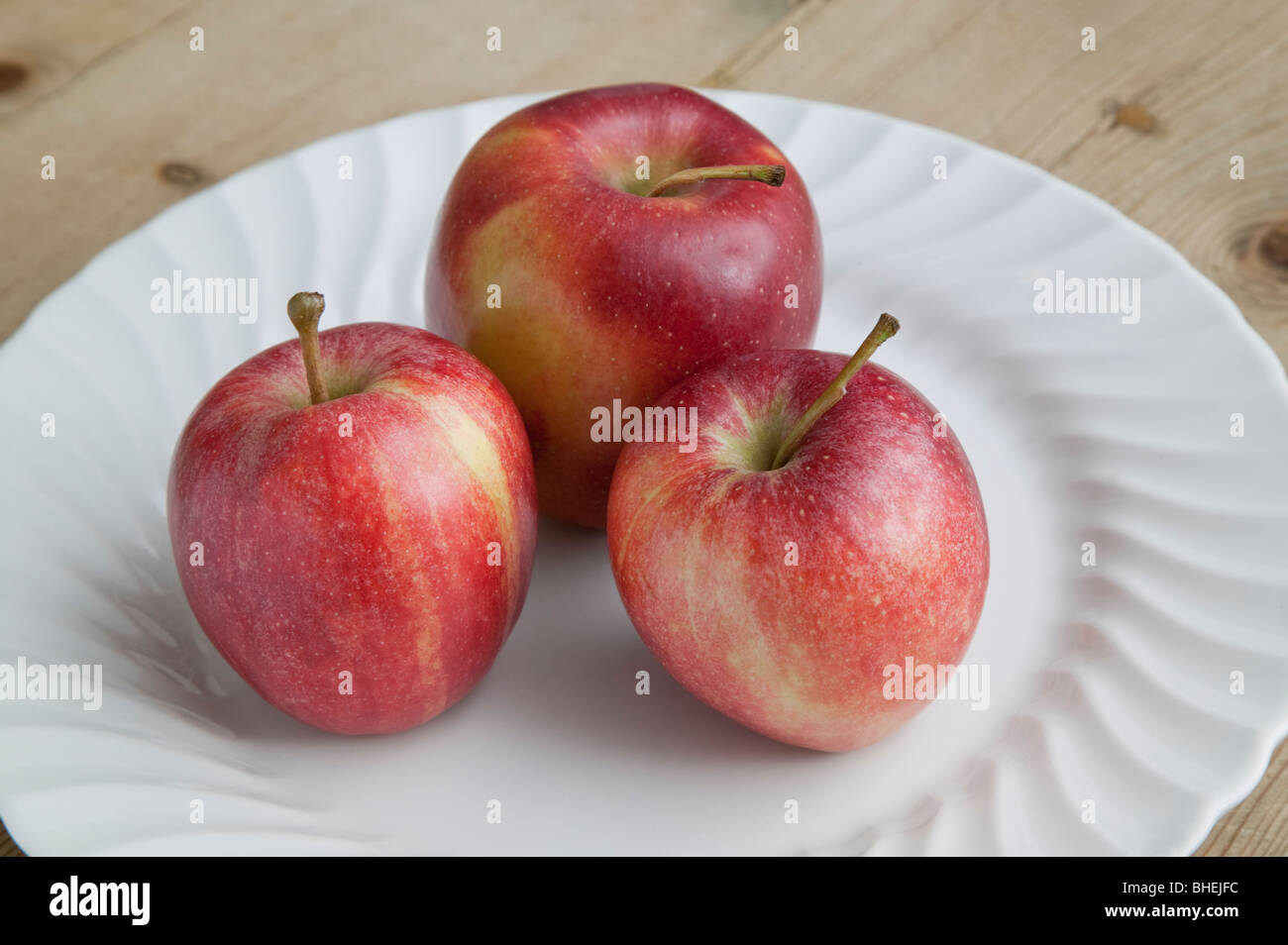 RED EATING APPLES ON WHITE PLATE ON WOODEN TABLE - Stock Image