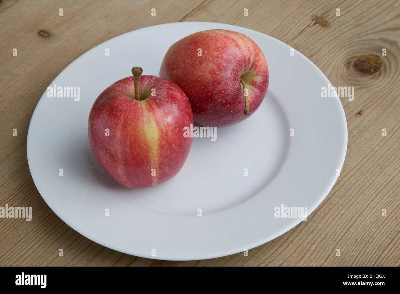 RED EATING APPLES ON WHITE PLATE ON WOODEN TABLE. - Stock Image