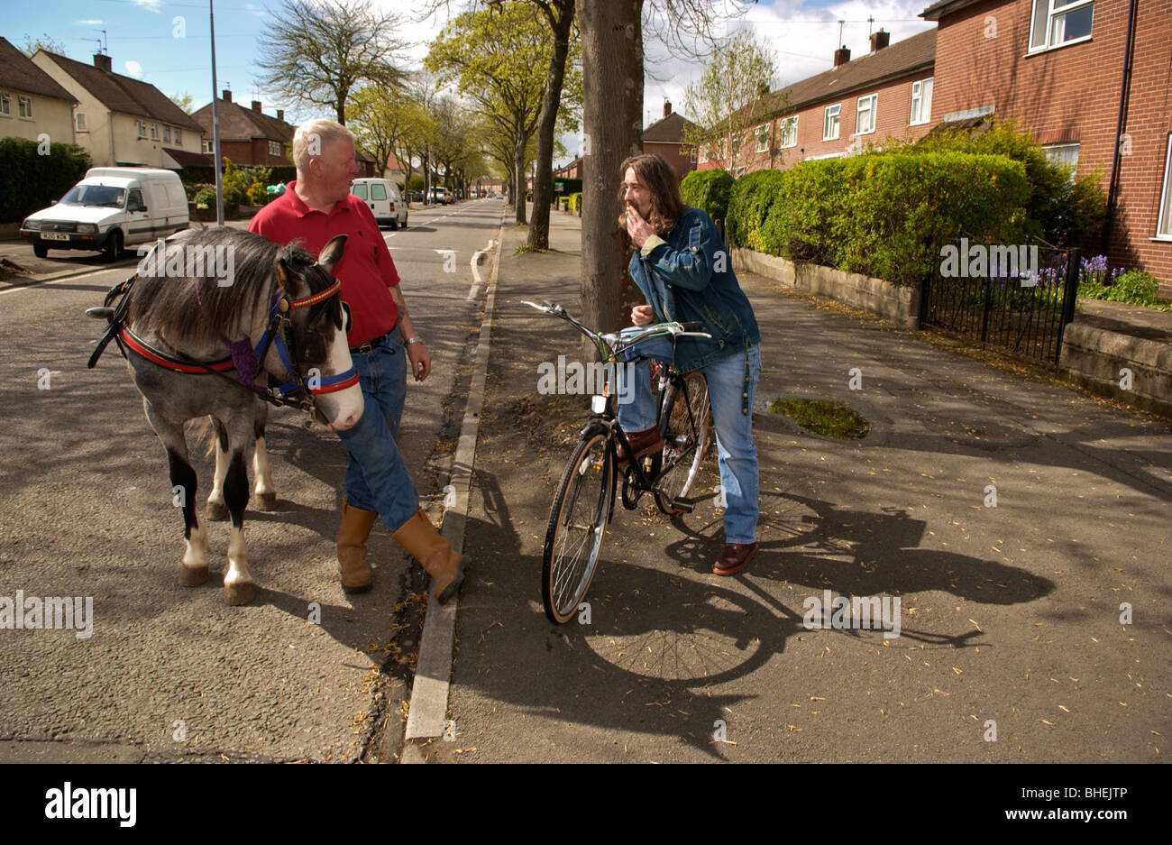 Man with pony and trap chatting to man with bicycle on street in suburb of Cardiff South Wales UK - Stock Image