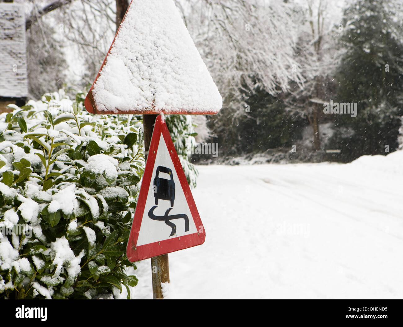 Danger, slippery road sign in winter. - Stock Image