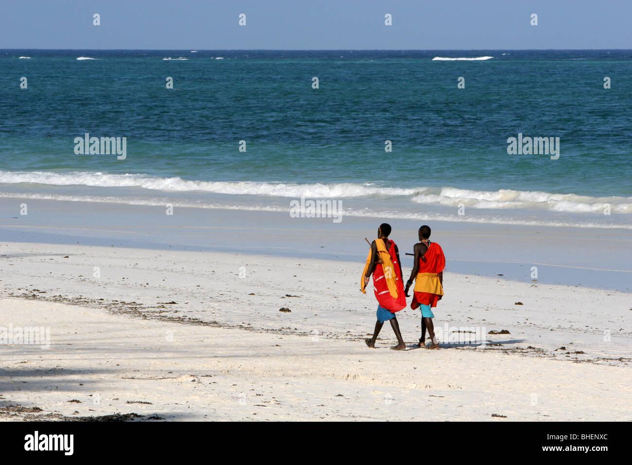 Kenyan Masai walking the beach by the Indian Ocean at Diani, Kenya - Stock Image