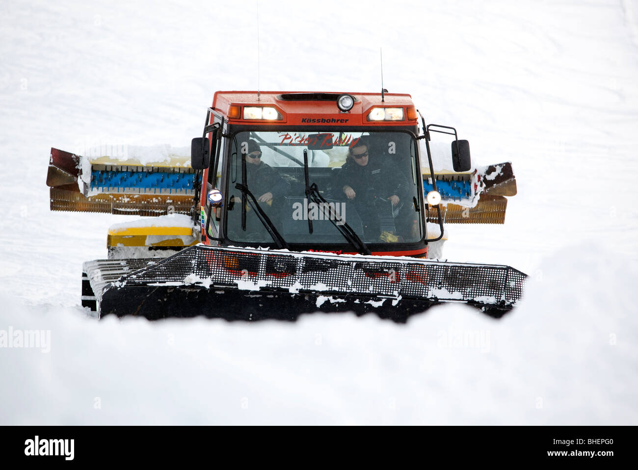 A piste tractor operating in the Cairngorms, Scottish Highlands in deep winter snow. - Stock Image