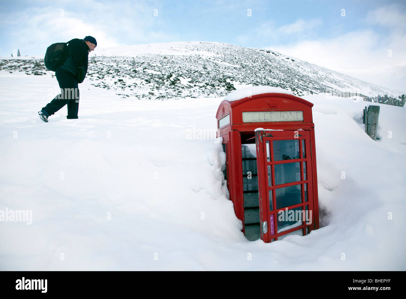 Deep snow almost buries a traditional red telephone box on the mountains in Aviemore, Cairgorms, Scotland. - Stock Image