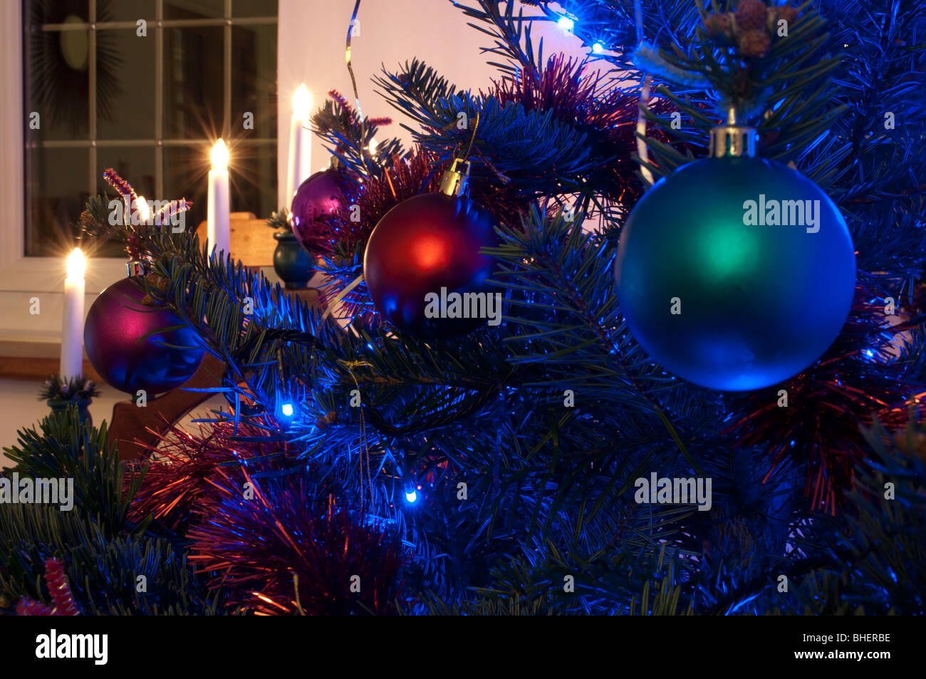 Christmas tree decorations with candles in background - Stock Image