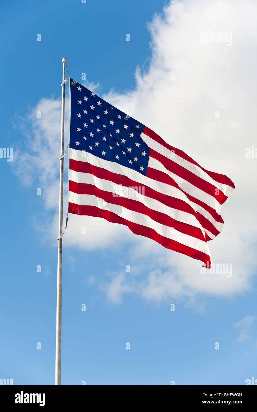 American flag waving in light blue sky with white clouds - Stock Image