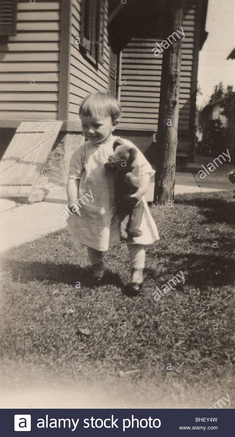 Young boy with stuffed toy, outdoors in front of the house 1920s - Stock Image