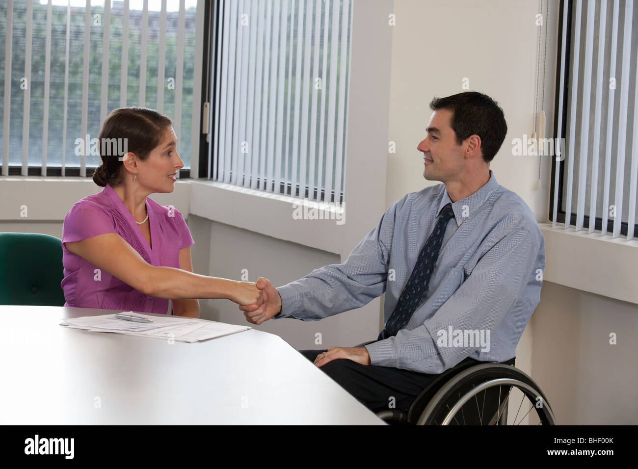 Handicapped businessman shaking hand with a businesswoman - Stock Image