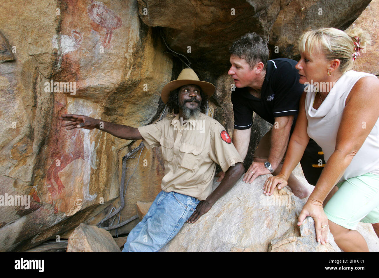 Aboriginal elder Peter Bolgi interprets rock art at a cultural site in the escarpment of Nitmiluk National Park, - Stock Image