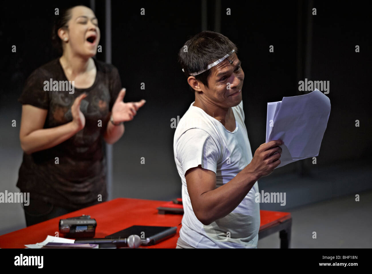 Thai actors on stage rehearsing and reading script. Thailand S. E. Asia - Stock Image