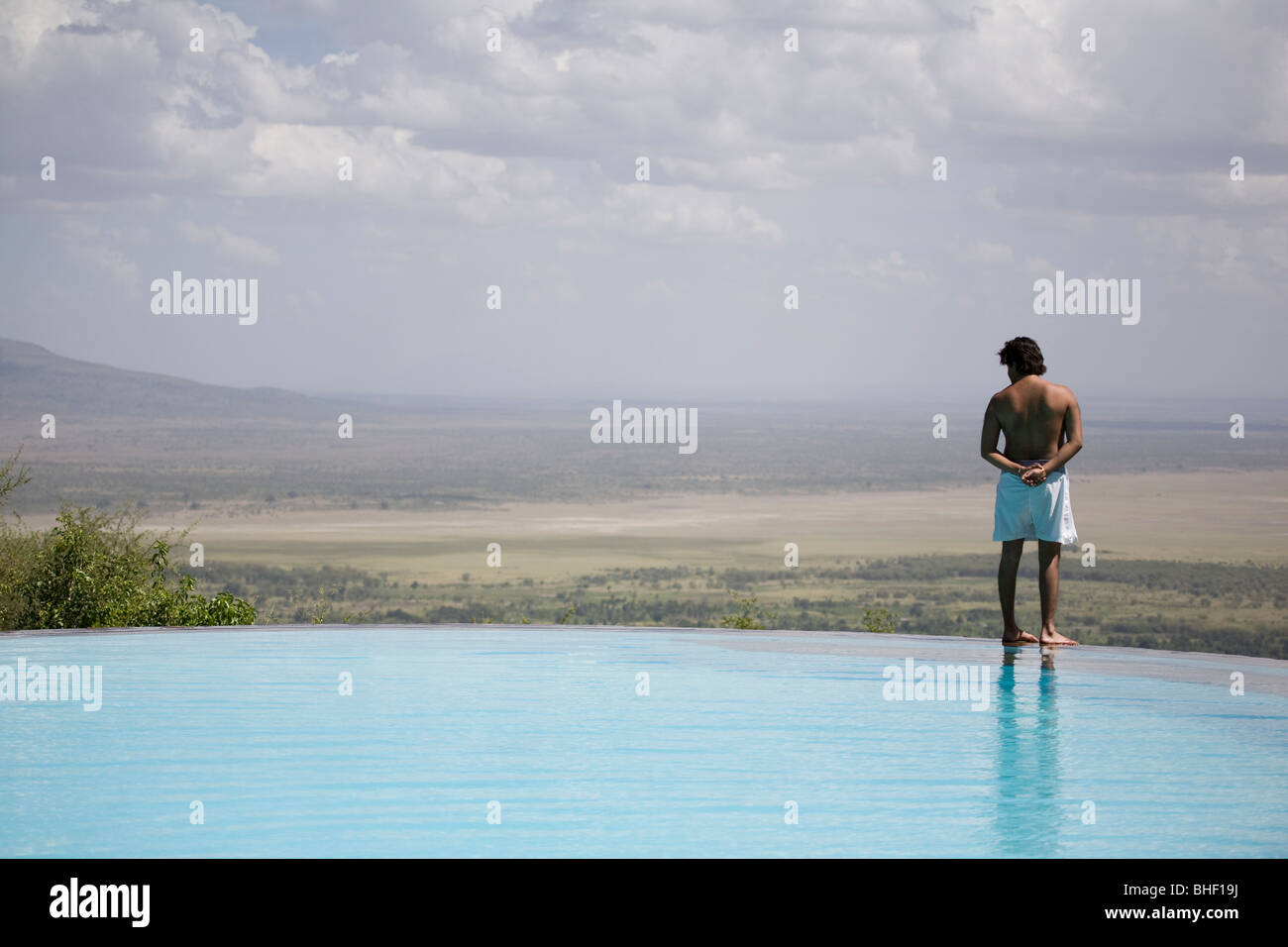 Bather by outdoor swimming pool at the Serena Manyara Lodge, Tanzania - Stock Image