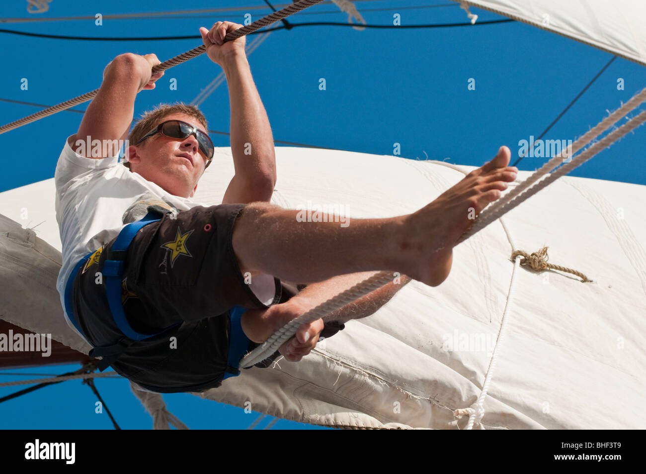 Crew of the square-rigged tall ship Solway Lass working aloft under sail - Stock Image