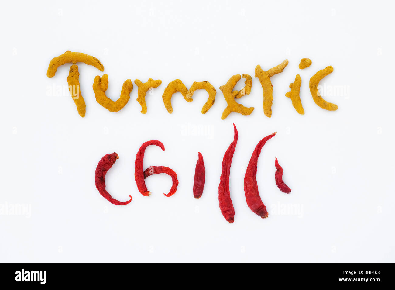 The word Turmeric and Chilli spelt in dried turmeric rhizomes and dried red chilli's on a white background - Stock Image