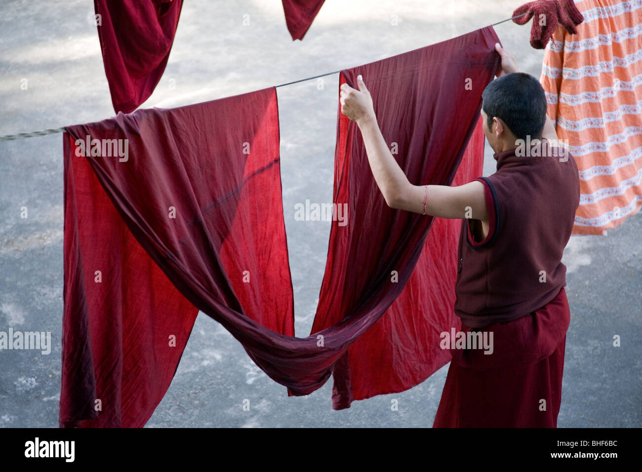 Buddhist monk putting a robe on the clothes line. McLeod Ganj. Dharamsala. India - Stock Image