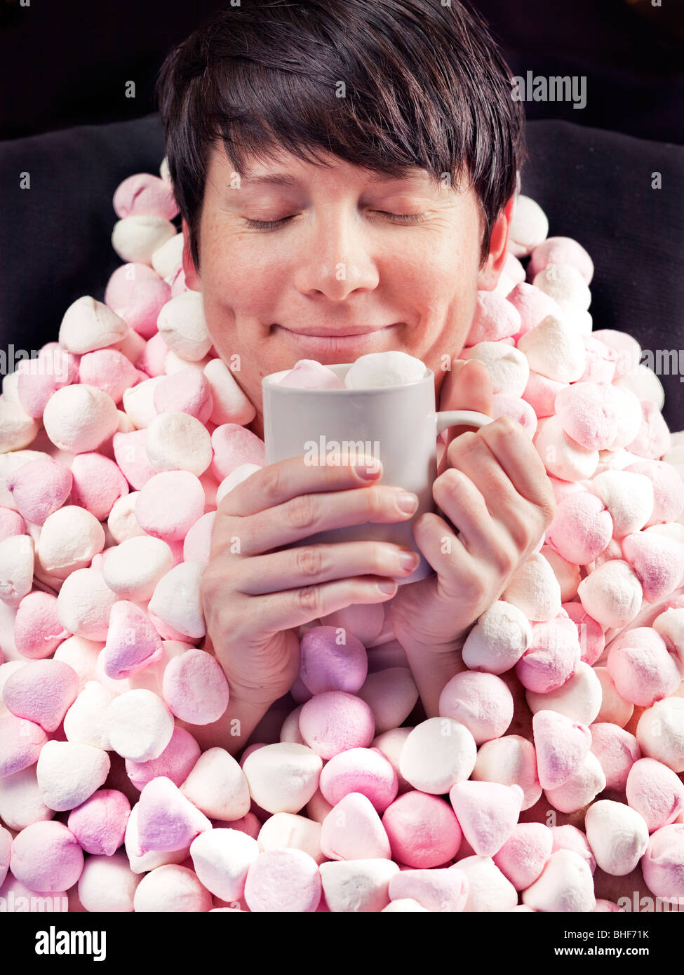 Woman with marshmallow blanket and hot chocolate - Stock Image