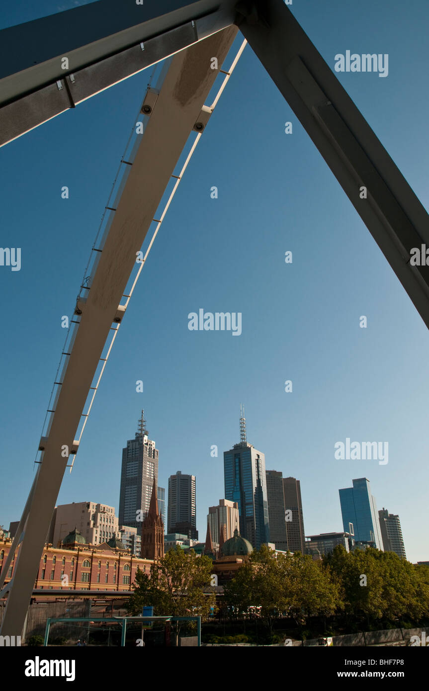 The Melbourne CBD framed in the arches of a modern bridge crossing the Yarra River into Docklands. - Stock Image