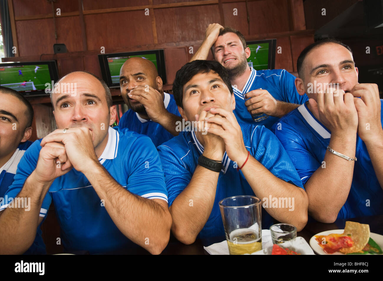 Worried teammates watching television in sports bar Stock Photo