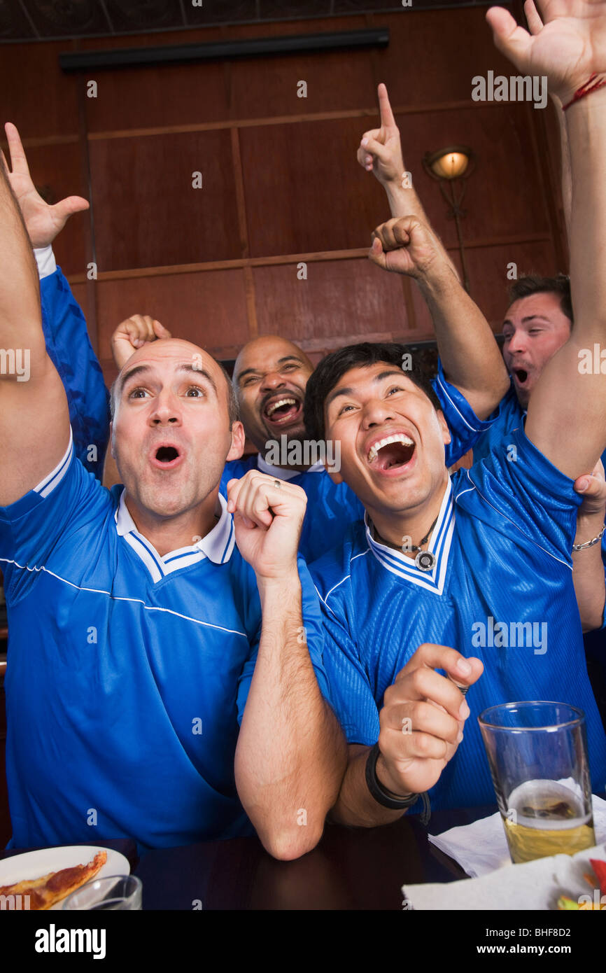 Cheering teammates watching television in sports bar Stock Photo
