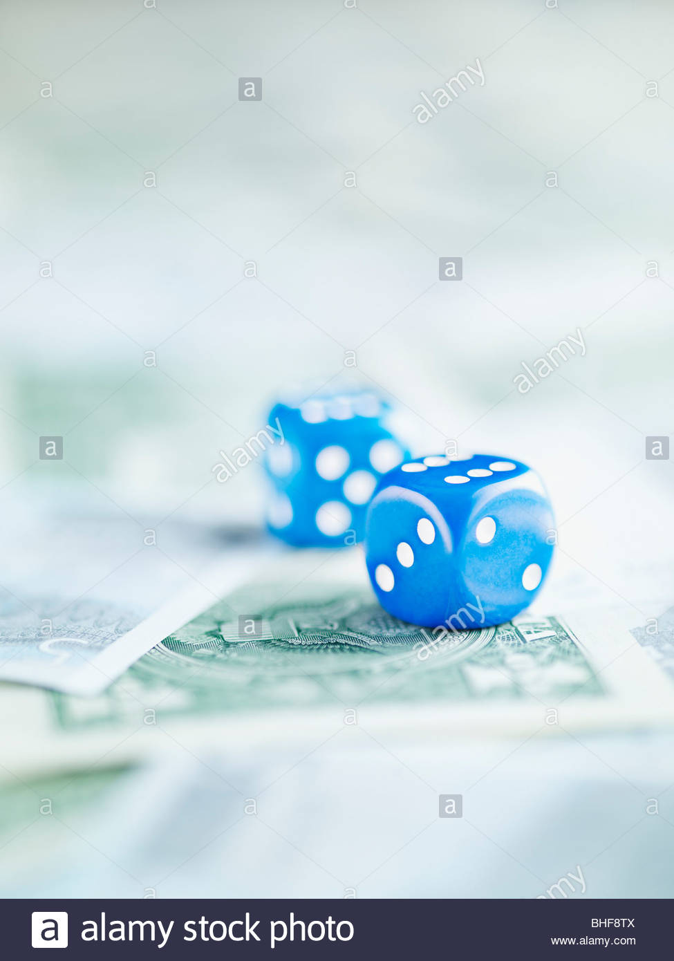 Blue dice on pile of dollar bills - Stock Image