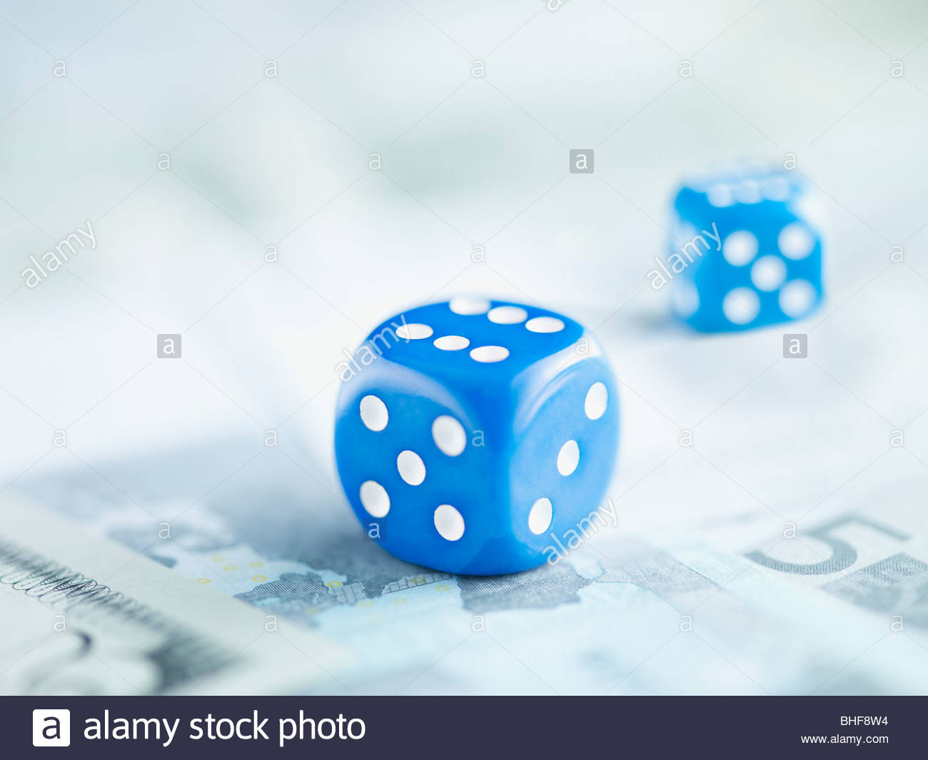 Two blue dice on pile of euro notes - Stock Image