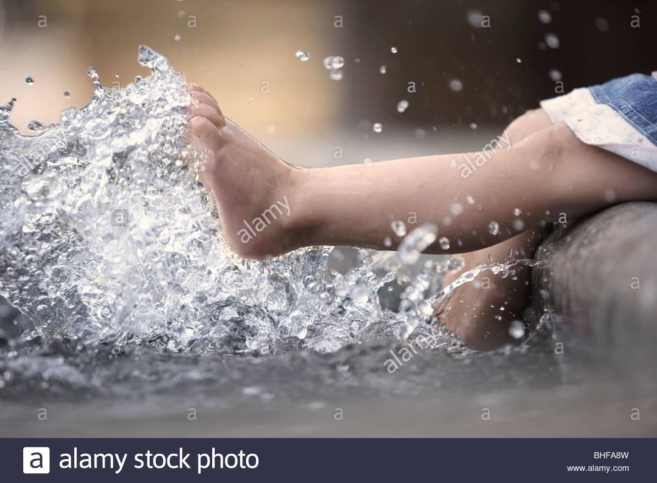 Barefoot girl splashing water - Stock Image
