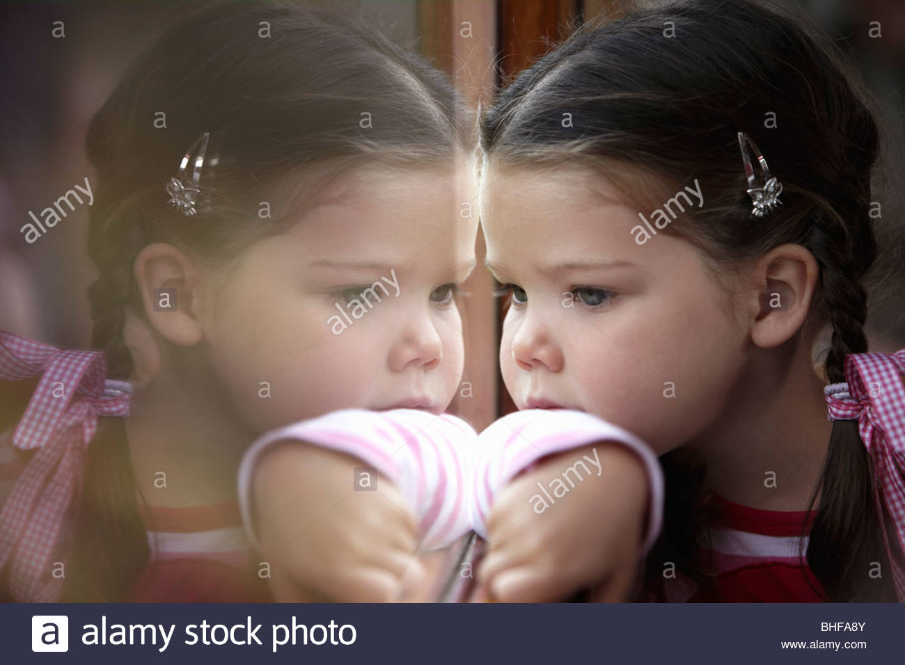 Girl and her reflection in window - Stock Image