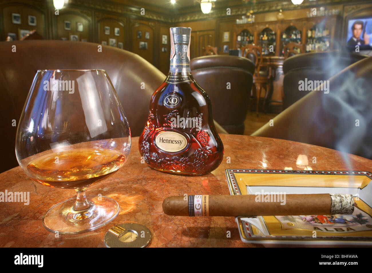 A glass of whiskey and a smoking cigar at the cigar lounge at ...