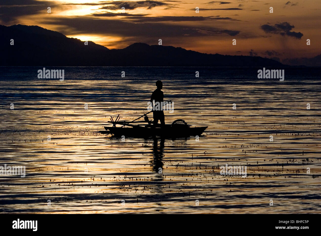 Man standing paddling in a canoo at sunset, New Britain, Papua New Guinea, Oceania Stock Photo