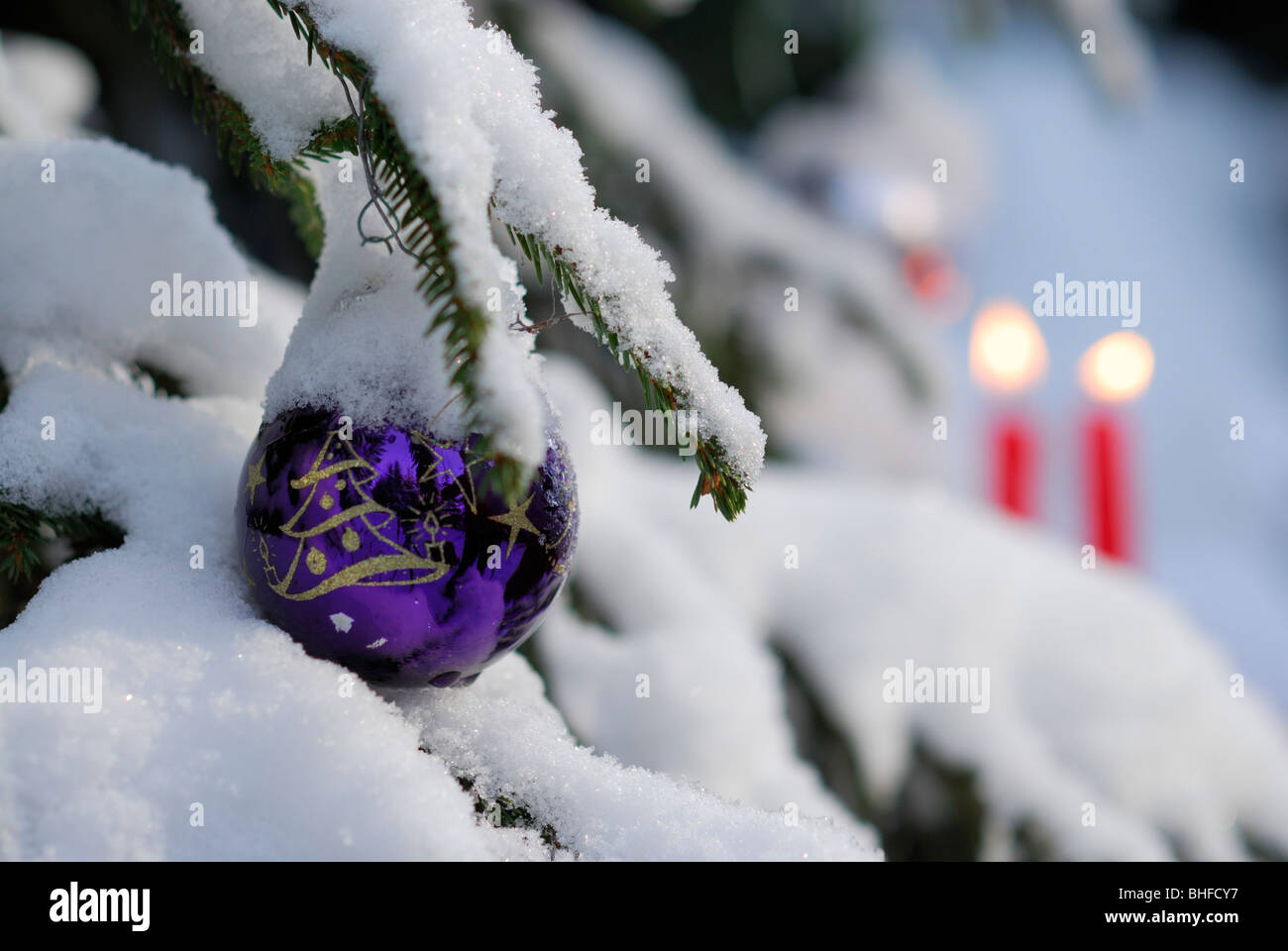 Christmas bauble hanging at snowcovered Christmastree with burning candles in background - Stock Image