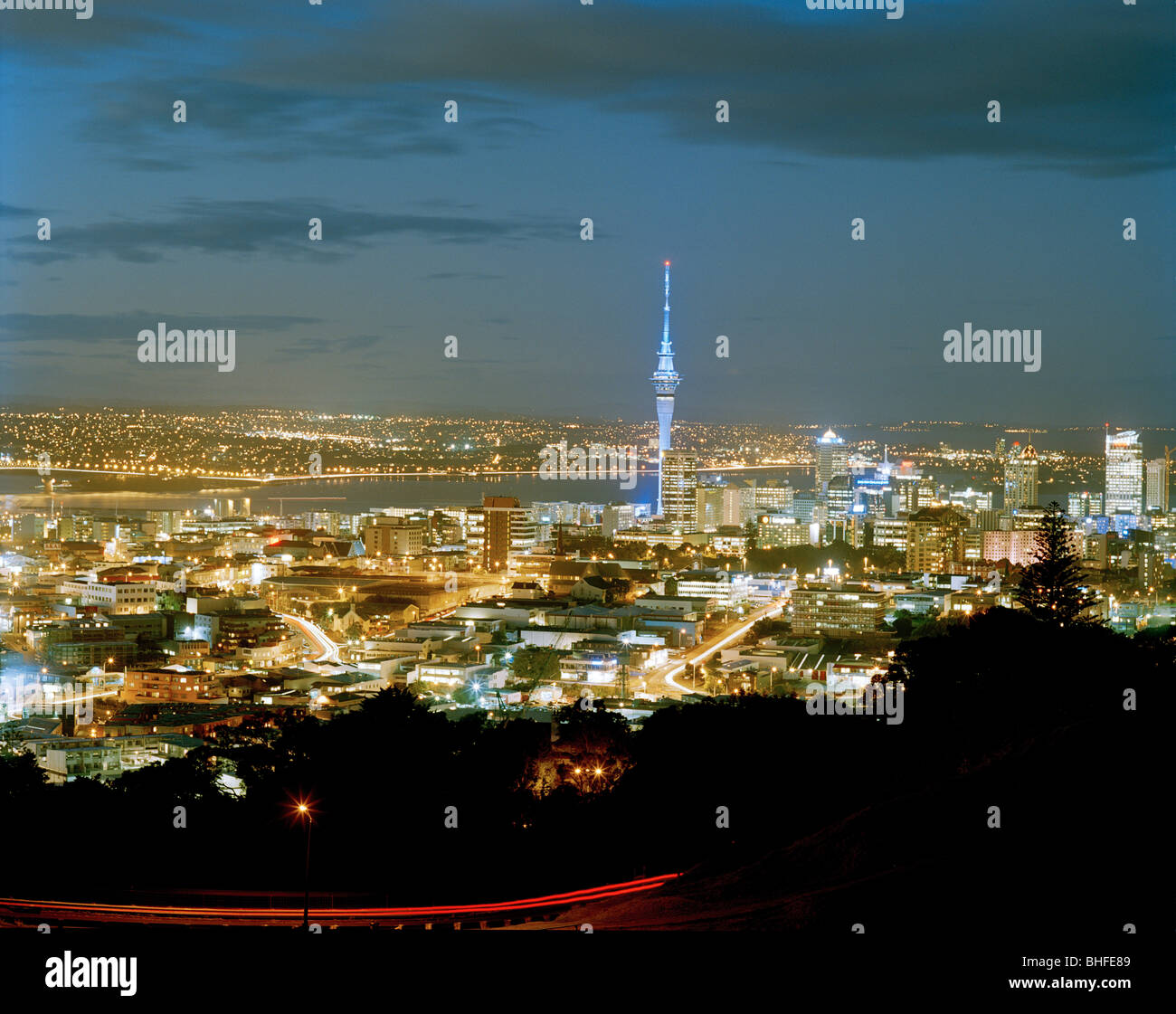 View at the illuminated Central Business District with Sky Tower at night, Auckland, North Island, New Zealand - Stock Image