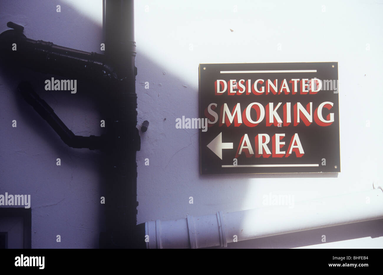 Sign on white wall surrounded by drainpipes stating with a direction arrow Designated Smoking Area - Stock Image