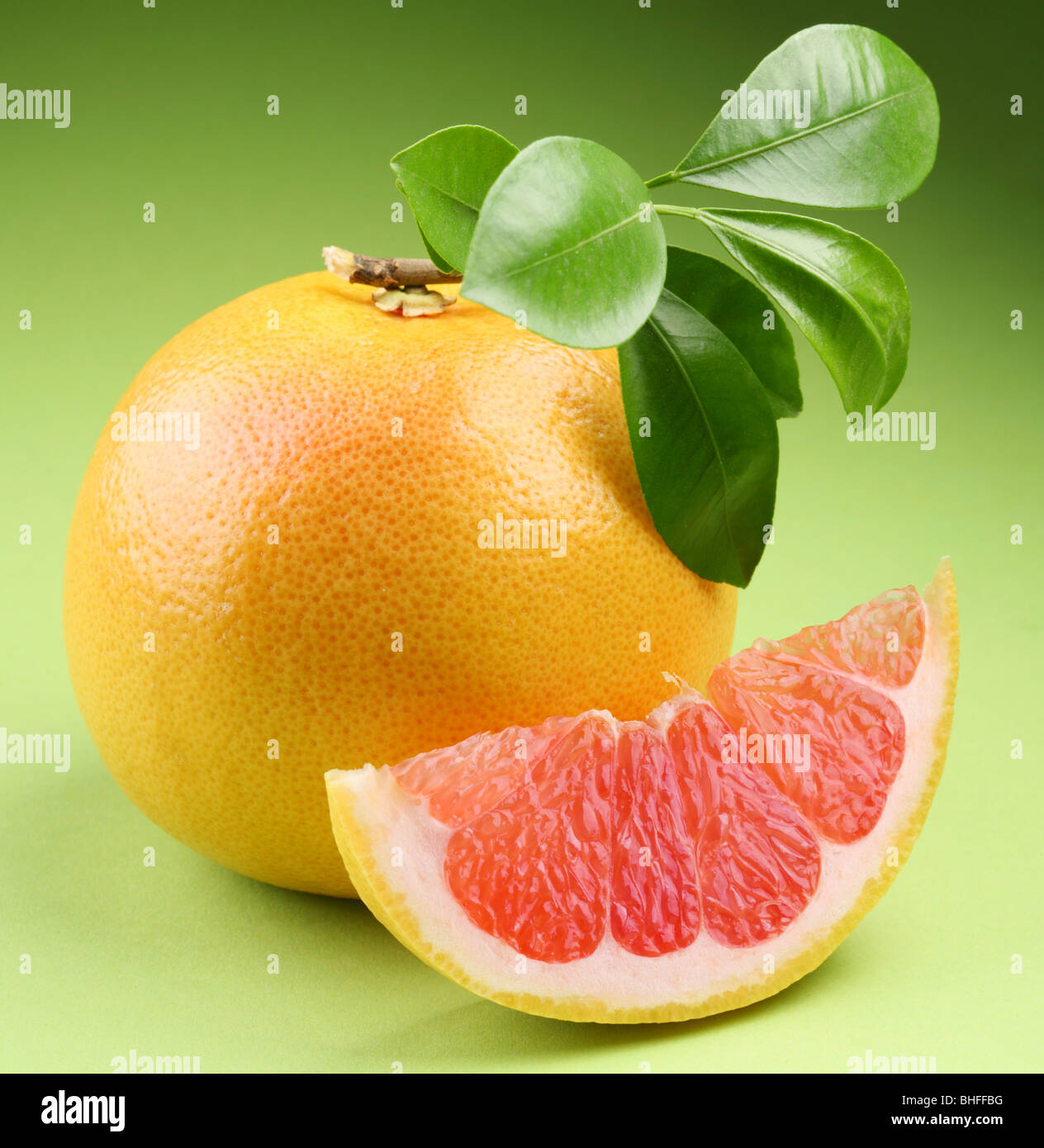 Ripe grapefruit with segment on a green background - Stock Image