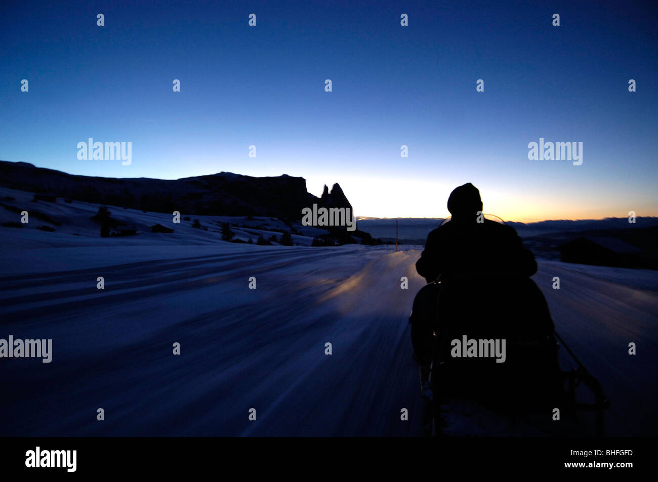 Man on a skidoo in the evening light, Seiser Alm, Schlern, South Tyrol, Italy Stock Photo