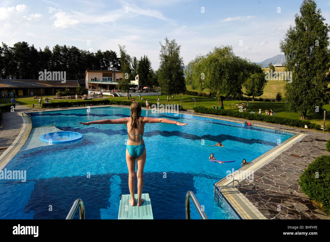 A girl standing on the diving board of the swimming pool at ...