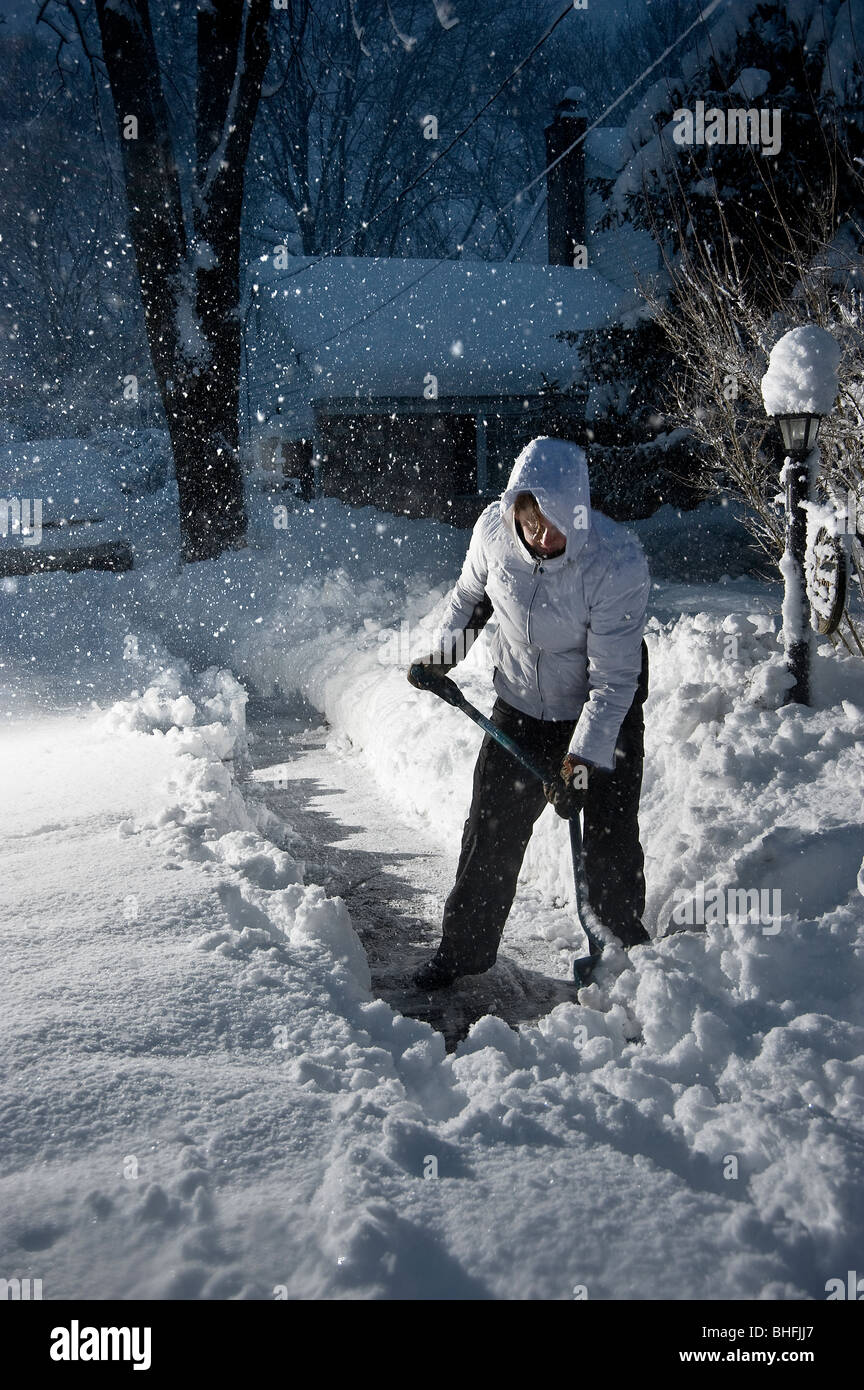 Shoveling Snow At Night While Snowing, Pennsylvania, USA - Stock Image