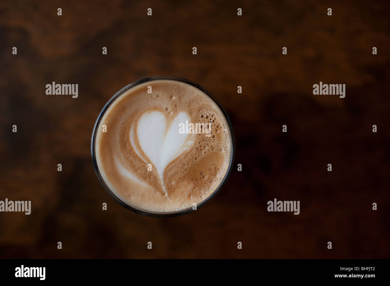 A love heart drawn in 'latte art' on top of a tall cafe latte coffee. - Stock Image