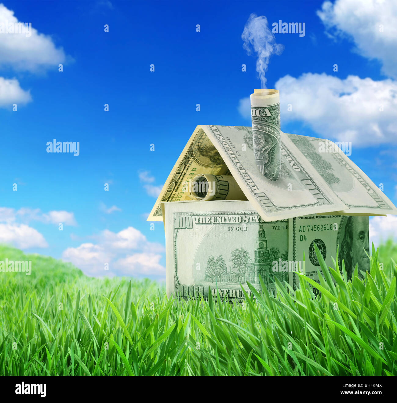 Dollar house in a green grass field over blue sky - Stock Image