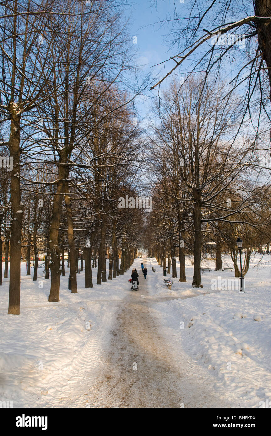 People walking through Humlegården park in Stockholm on a cold winter's day. - Stock Image