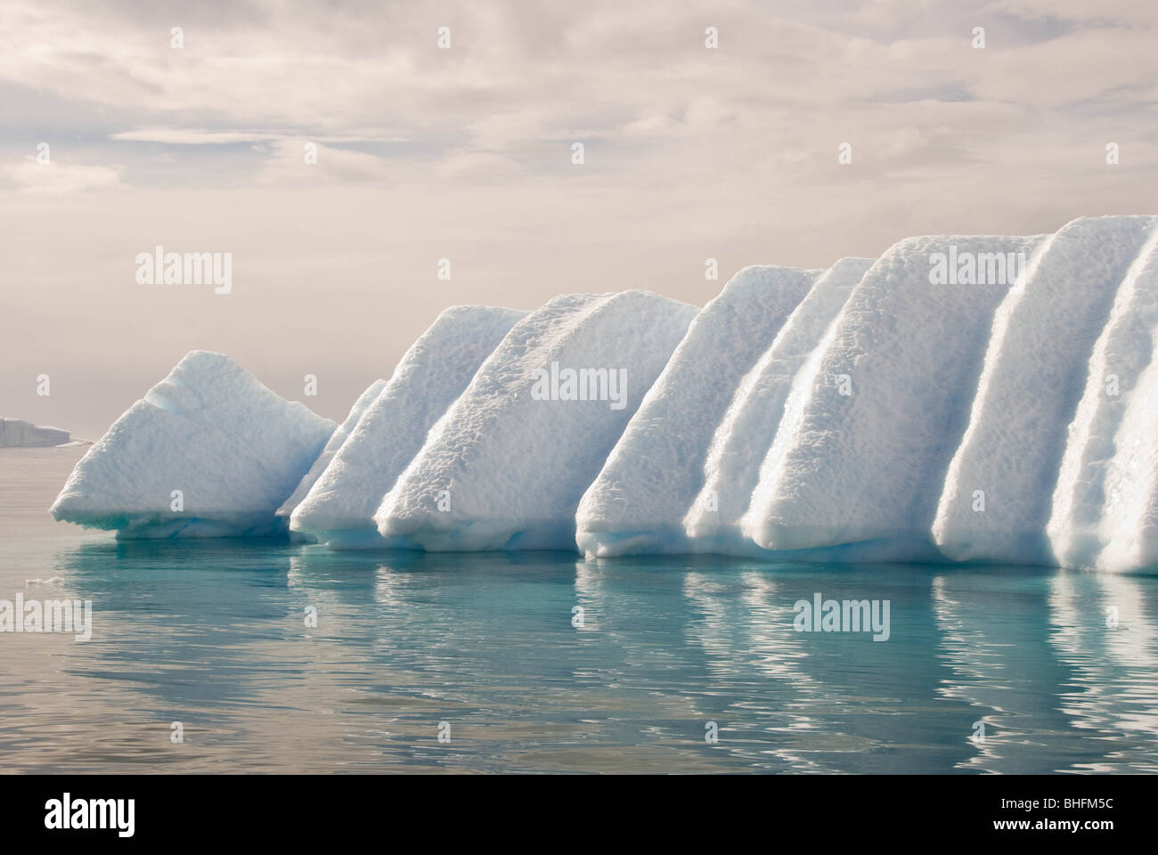 The melting of an iceberg exploiting weaknesses due to the original snow layering creates an unusual shape. - Stock Image