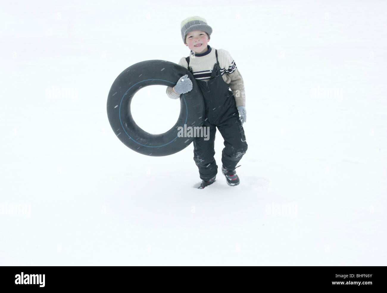 portrait of boy with inner tube in snow - Stock Image