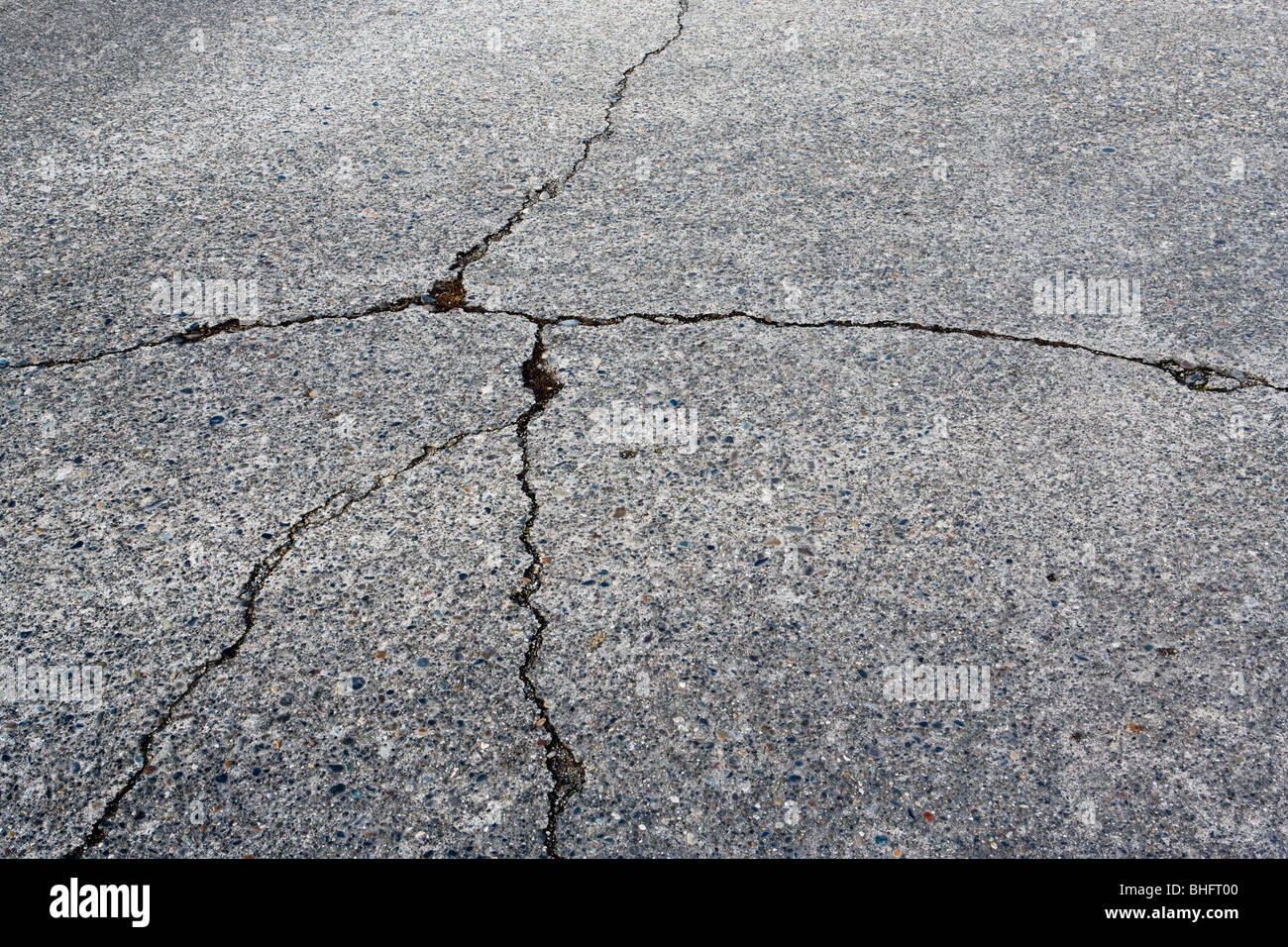 A cracked concrete street. - Stock Image