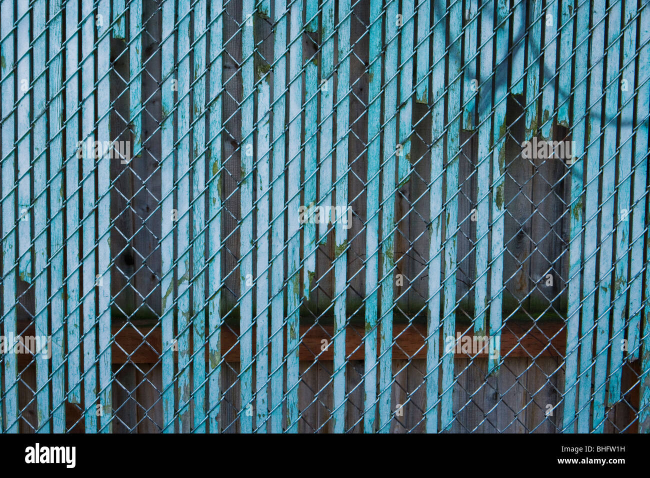 An old chain-link fence with broken wooden slats. - Stock Image