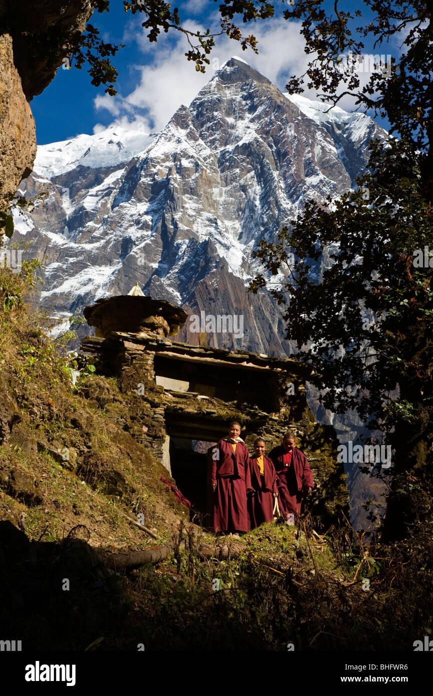 BUDDHIST NUNS walks through a CHORTEN gateway in the NUPRI AREA - AROUND MANASLU TREK, NEPAL - Stock Image