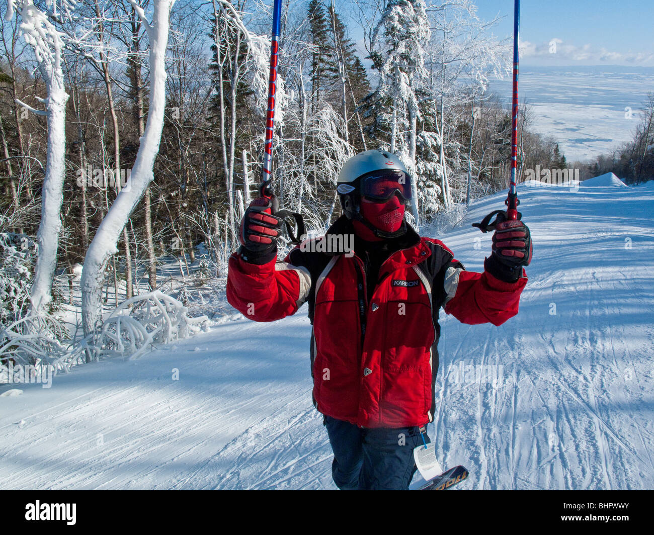 A downhill skier in red jacket with ski poles in the air at Le Massif in Quebec Canada - Stock Image