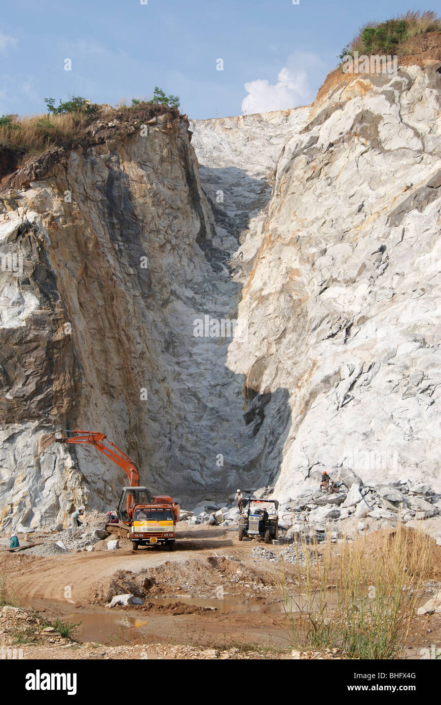 Huge Rock quarry.Natural environment (breaking Hills) destruction by Humans using machinery (Lorry and Earth movers - Stock Image
