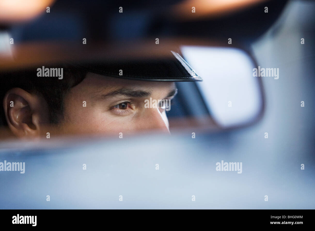 Chauffeur reflected in rear view mirror - Stock Image