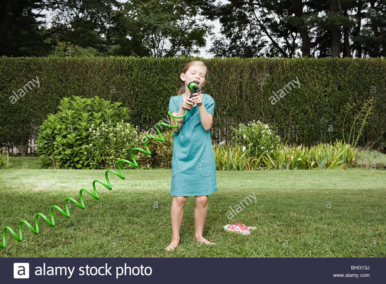 Girl singing into a garden hose - Stock Image